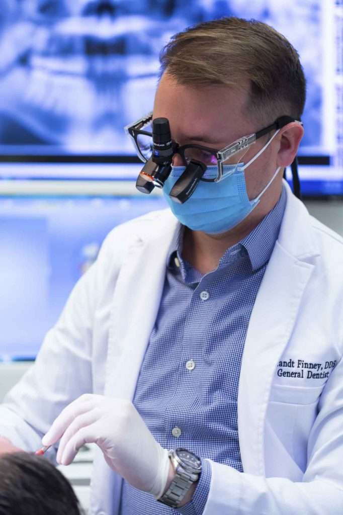 dr brant finney, a dentist at bloomington indiana, examines a patient's teeth